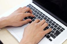 A transcriptionist typing on a laptop.