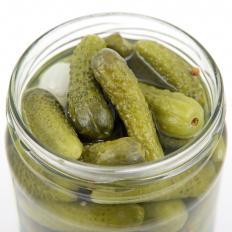 A jar of pickled gherkins. Pickles are usually made with vinegar, which helps preserve them.