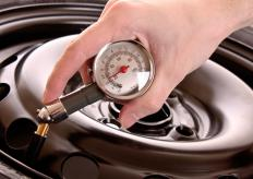 A man checks the air pressure in a car tire with a dial tire pressure gauge.