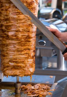 Doner meat for shawarma being cut off the spit with a knife.