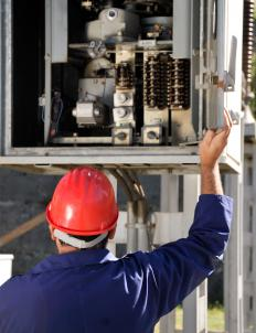 An electrical engineer inspecting a circuit breaker.