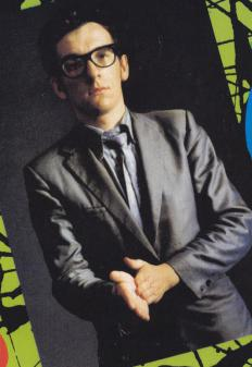 Elvis Costello wears horn-rimmed glasses.