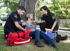 Two EMTs helping a woman.