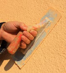 A person finishing colored stucco.