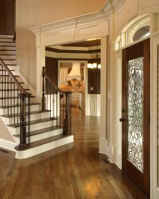 Golden paint and crown molding give the appearance of a bright entryway.