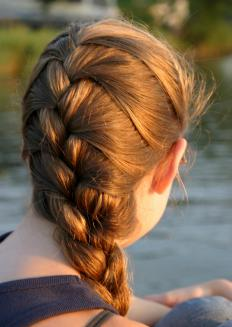 Some people French braid hair before putting it in a bun.