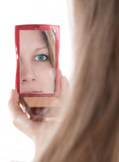 A woman looking in a compact mirror.