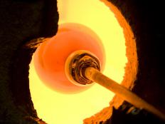 Glass blower heating glass in a kiln.