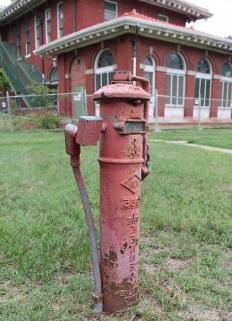 A ground post indicator valve features a tall, vertical post with a lower portion that is buried in the ground with the purpose of opening or closing a water supply to fire protection systems in a building.