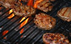 Hamburgers cooking on a grill.