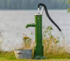 A hand water pump uses the power of suction to deliver water from an underground well.