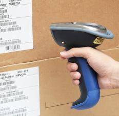 A cashier uses a handheld barcode scanner to check the price on an item.