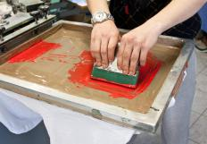 The operator uses a squeegee to press ink through to the material in screen printing.