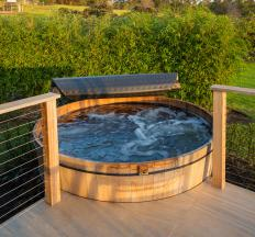 A wood-fired hot tub uses heat from a fire in a stove to warm the water, which means no electricity is necessary to heat the tub.
