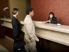 A hotel front desk employee checking in guests.