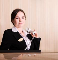 A hotel hostess is responsible for checking guests into their rooms.