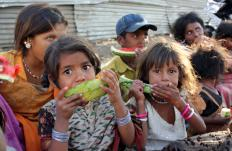 Impoverished children eating watermelon