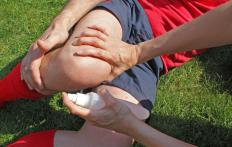 An athletic trainer provides first aid when an athlete is injured on the field.