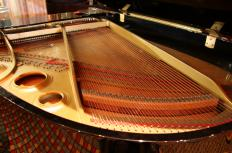 The strings of a piano are struck by hammers to make sound.