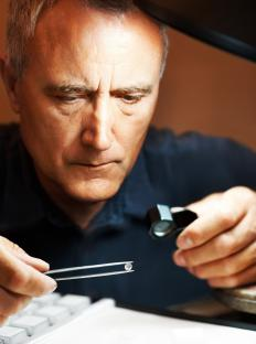 A jeweler using tools to inspect a gem.