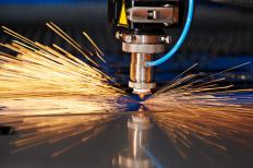 A laser cutter is used to cut a sheet of metal. Software is typically used to control the beam.