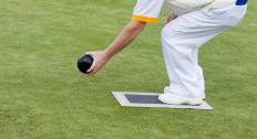 Players take turns rolling a ball in lawn bowling.