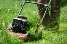 A push lawn mower is pushed by an owner to cut grass.