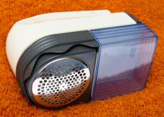 To remove pilling, a lint shaver is turned on and brushed over the surface of the fabric.