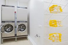 A pair of stacked washers and dryers in a locker room.