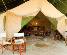 A tent decked out with a full bed, rug, and furniture makes adventure luxurious.