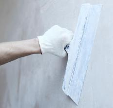 A man uses a taping knife to skim coat a green drywall panel.