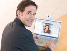 Video conferencing equipment allows people that aren't physically present to participate in the boardroom meeting via computer.