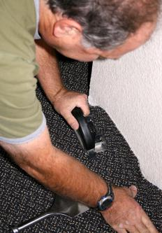 After a carpet is hooked onto the gripper tacks, the excess is trimmed away.