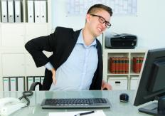 Long periods of sitting at a desk may cause back pain.