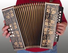 An accordion reed is contained within the bellows of an accordion.