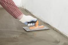 A man smoothing out hydraulic cement on a basement floor.