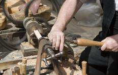 A wood turning chisel is used to cut wood that's being rapidly turned on a lathe.