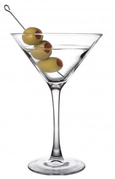 A martini with three thrown olives.