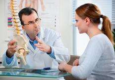 A chiropractor talking to a patient.