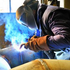 A person MIG welding a large pipe.