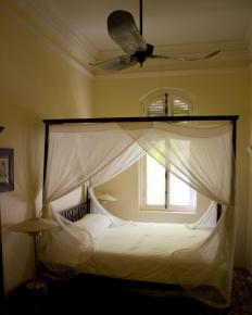 A bed with mosquito netting.