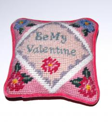 Needlepoint finishing is the process of turning a stitched needlepoint canvas into a decorative item or something for practical use, like a pillow.