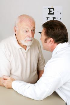 A low vision therapist examining a patient's eyes.
