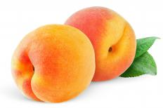 Peaches are cooked in syrup and then drizzled with Melba sauce to make Peach Melba.