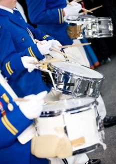 During a festival, marching bands compete by showcasing different styles of music and marching.