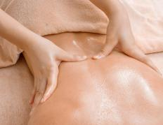 A masseuse may use a covered massage mat to provide additional comfort and pressure.
