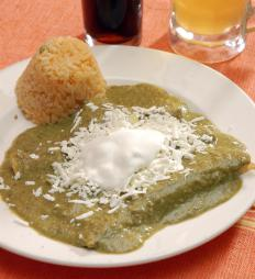 Salsa verde enchiladas topped with sour cream and queso fresco.