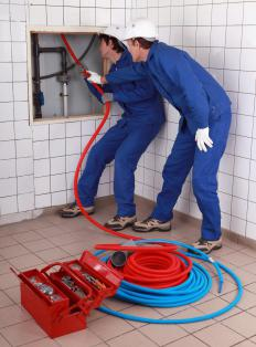A plumber and apprentice working.