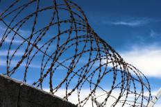 Chain link fencing featuring barbed wire is a popular choice for prisons.