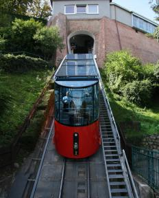A funicular runs up a steep incline with the help of tracks or cables.